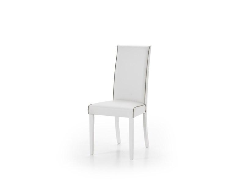Soggiorno in legno bianco con tavolo sedie mobile tv e credenza.